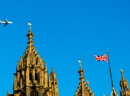 A light aircraft soars above the tips of the spires on the Palace of Westminster. The sky is a deep hue of blue on what is clearly a summer day.